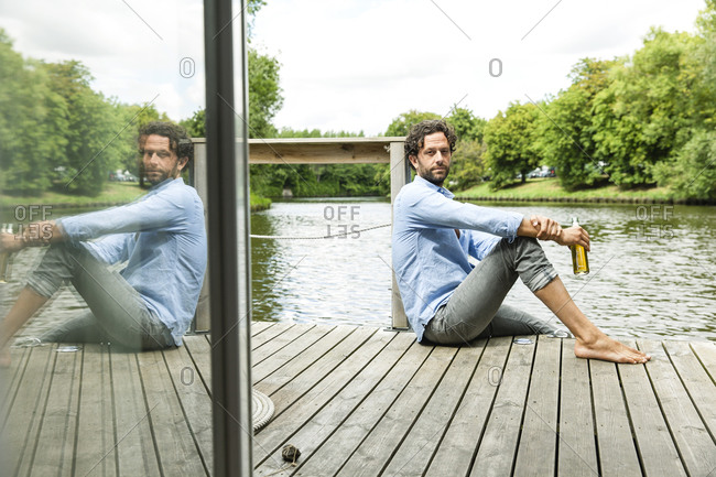 Man sitting on platform at the waterside with beer bottle