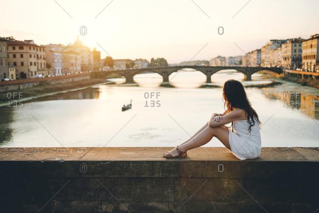 Woman wearing white summer dress sitting on a bridge at sunset