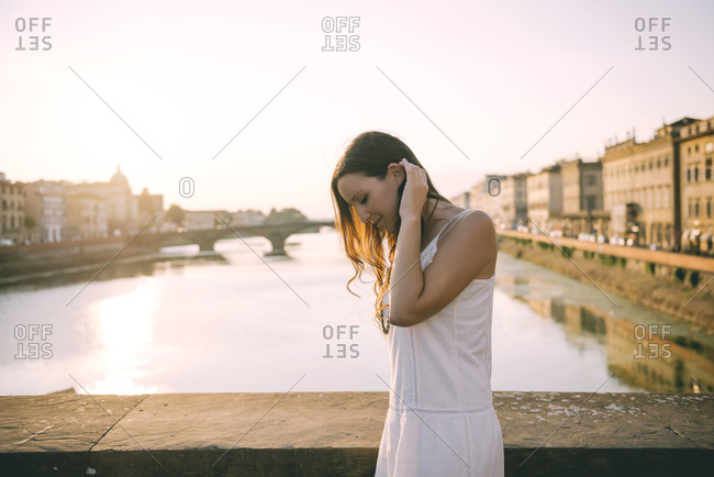 Happy woman wearing white summer dress standing on a bridge at sunset