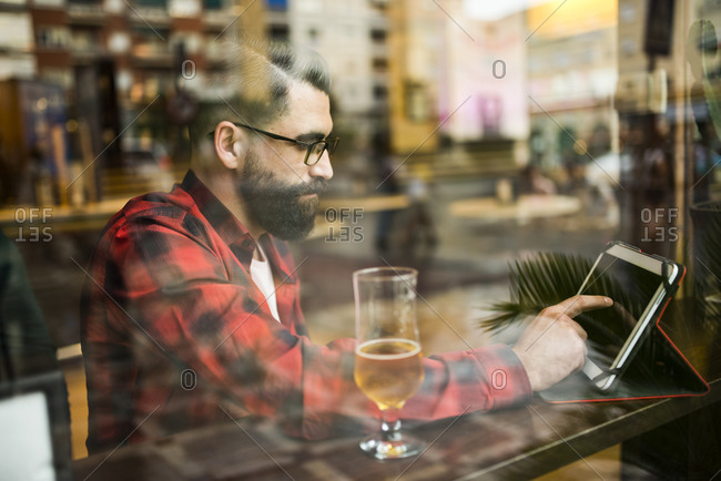 Adult bearded hipster style man touching tablet in bar and drinking alcohol near to window