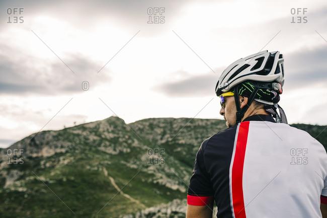 Mountain biker in extreme terrain, looking at landscape, Tarragona, Spain