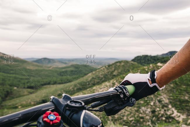 Mountain biker in extreme terrain, close up of handle bar, Tarragona, Spain