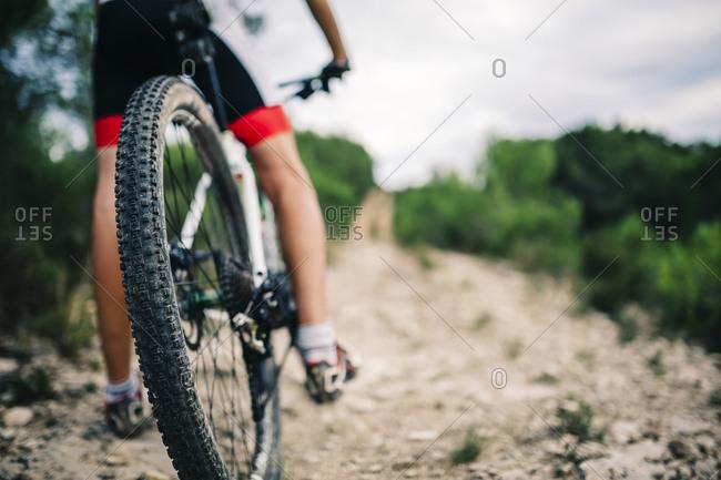 Mountain biker in extreme terrain, rear view, Tarragona, Spain