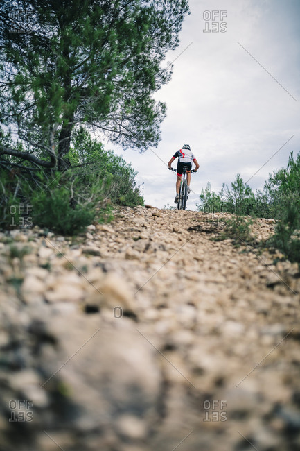 Mountain biker in extreme terrain, rear view, Tarragona, Spain