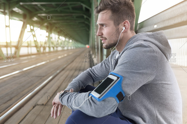 Young athletic man with earbuds and wearable computer sitting on bridge