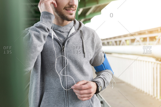Young athletic man with earbuds and wearable computer