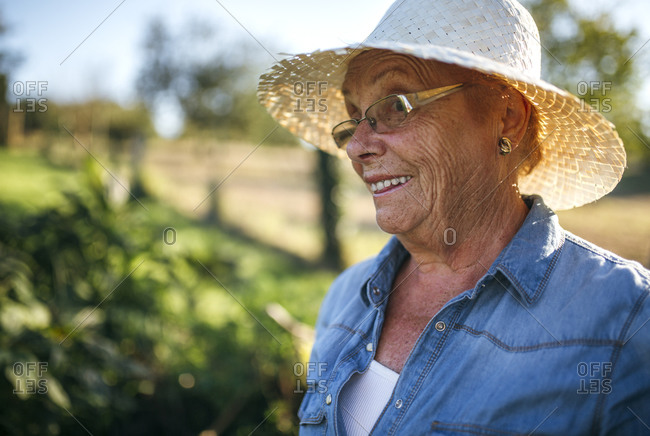 Portrait of smiling senior woman with straw hat in her garden