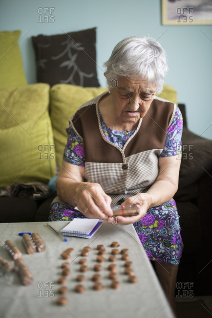 Senior woman sitting on couch at home counting Euro cent coins