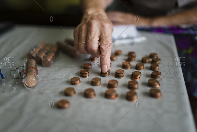 Elderly woman counting money and making stacks of Euro cents