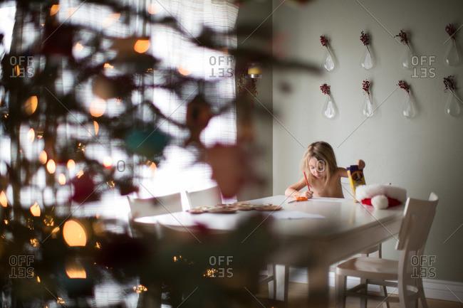 Girl drawing at table at Christmastime