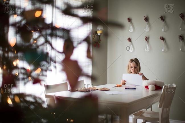Girl sitting at table at Christmastime