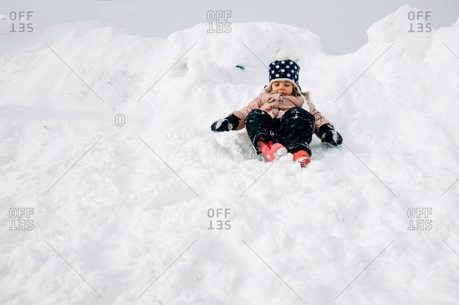 Girl sitting in a snow bank in winter