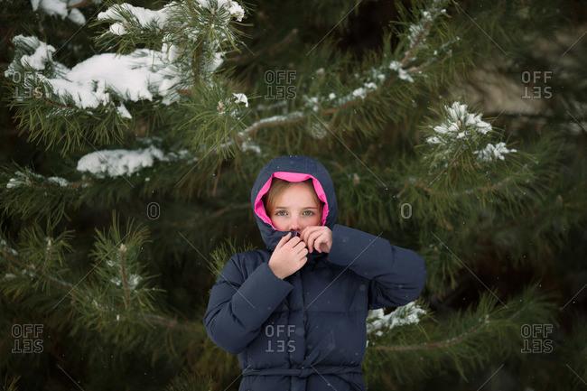 Girl zipping up jacket by fir tree in winter