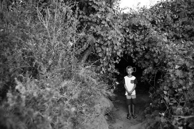 Young boy stands in opening of overgrown foliage