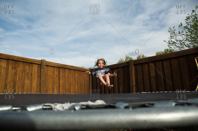 Young girl in midair above trampoline