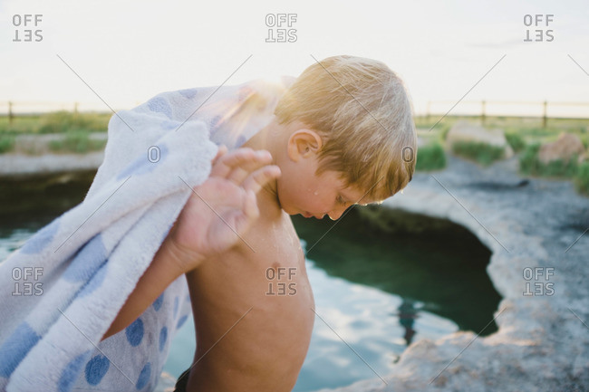 Boy with towel on edge of hot spring