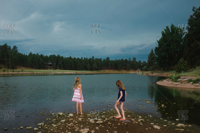 Two girls standing on shore of lake under dark cloudy sky