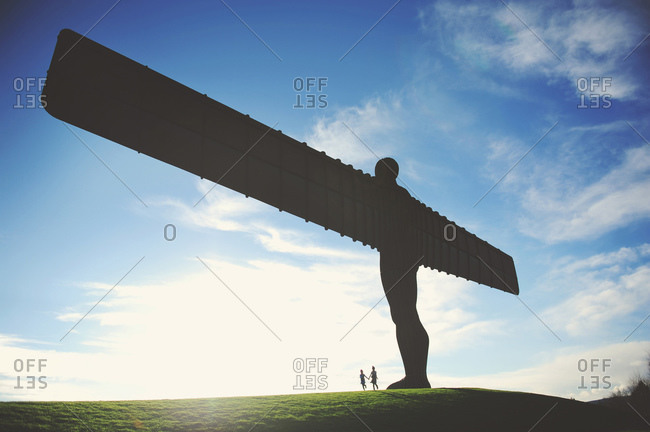 Two girls holding hands below the Angel of the North statue near Gateshead, England