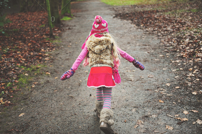 Little girl walking on a wet path in winter clothing