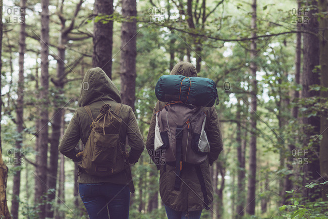 Two backpackers walking together in the woods