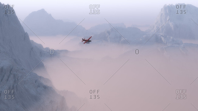 Airplane flying above snowy mountains and mist