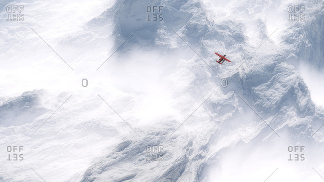 Airplane flying over snow covered mountains