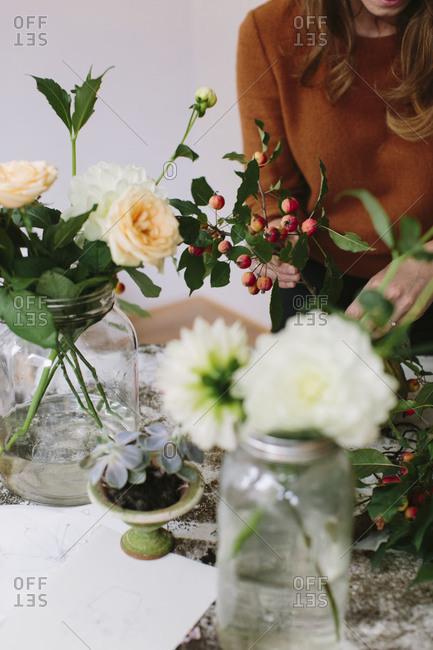 Floral designer creating arrangement in mason jars