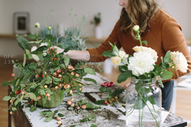 Designer creating flower arrangement in pottery vase with apple branches, white dahlias and peach roses