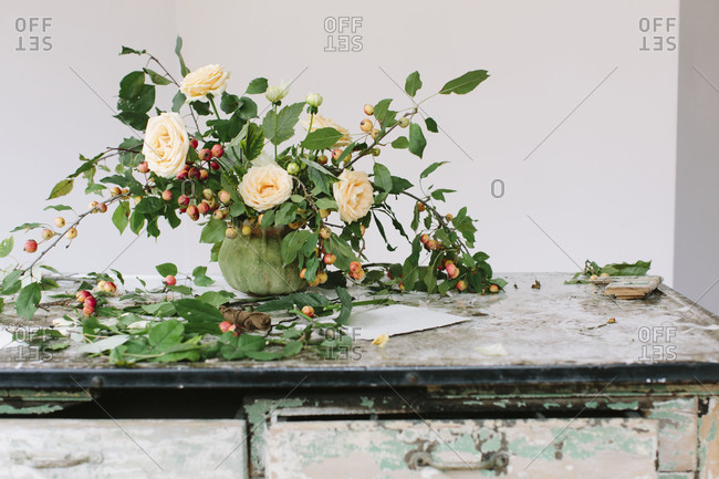 Elegantly rustic flower arrangement of apple branches and peach roses in vintage pot on rustic workbench