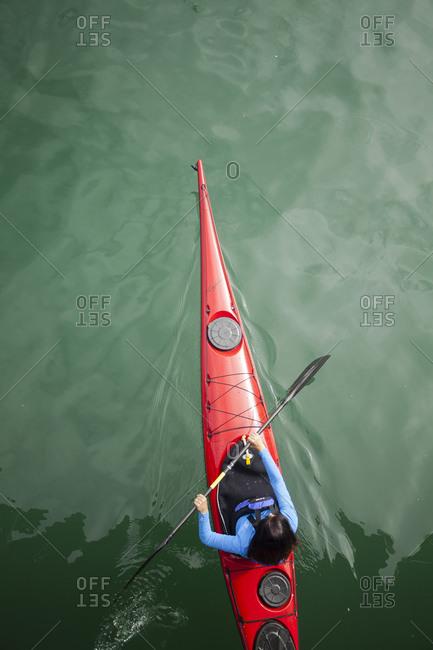 Woman paddling a sea kayak in Dana Point harbor, California