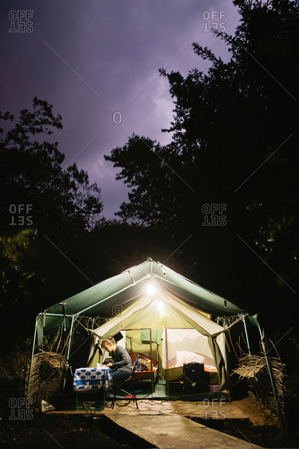 A woman at dusk in a safari tent in the Maasai Mara, Kenya