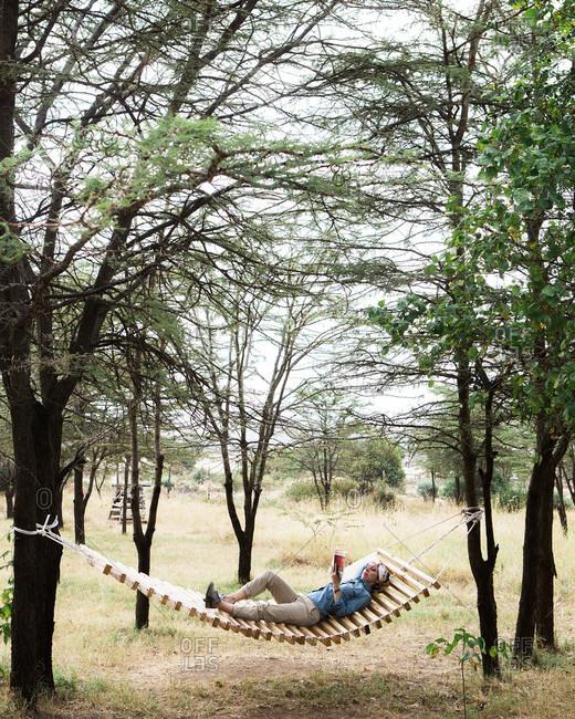 A woman relaxing and reading in a hammock in the Maasai Mara, Kenya on a safari