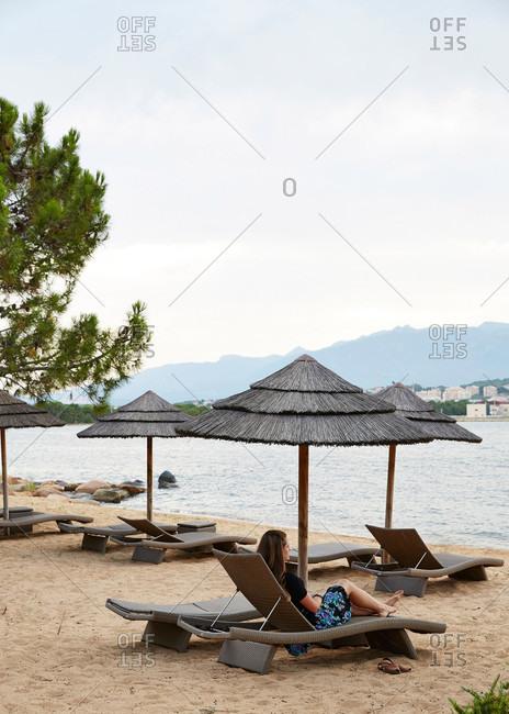 Porto Vecchio, Corsica, France - July 20, 2014: A woman lounging on a beach at Hotel Belvedere in Porto Vecchio, Corsica, France