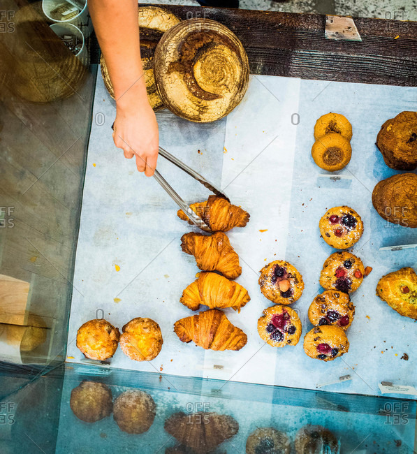 A hand reaches into a bakery display case to grab a croissant with silver tongs