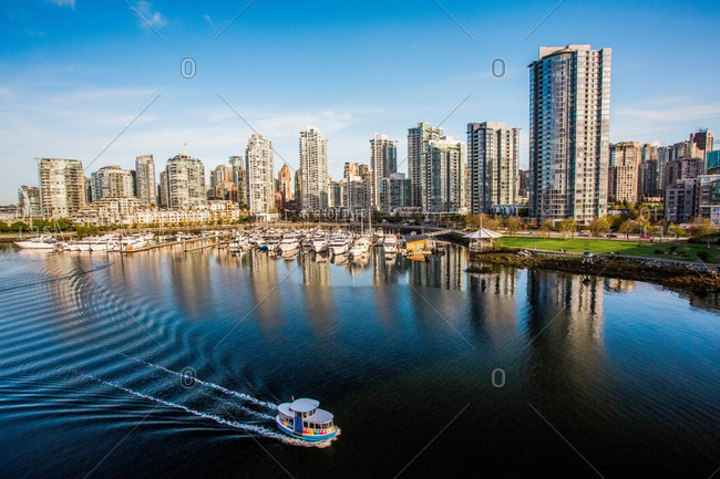 A small tourist boat moves through calm water of downtown Vancouver