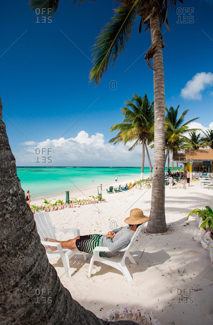 A man naps on a lounge chair below palm trees on a white sand beach