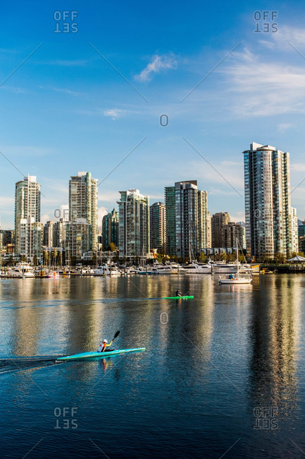 Two sea kayakers paddle through calm water with downtown Vancouver skyline in distance
