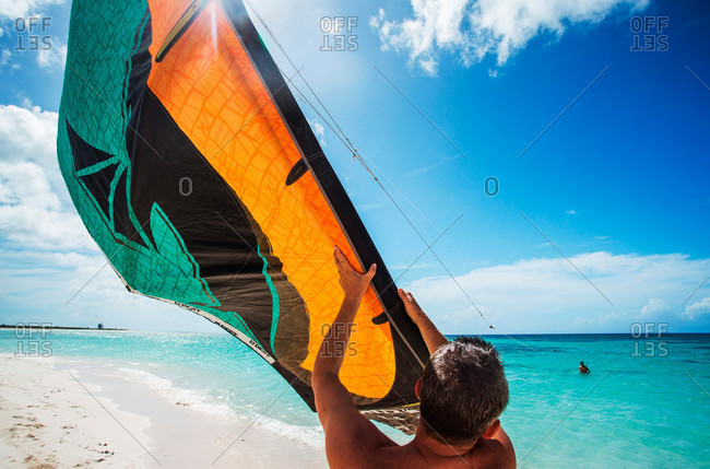 Kite boarder launches from white sand beach into the Caribbean water