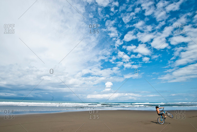 A Costa Rican boy rides his bike on a desolate beach on a sunny day