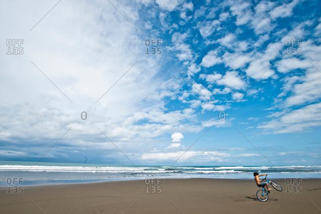 A Costa Rican boy rides his bike on a desolate beach on a sunny day