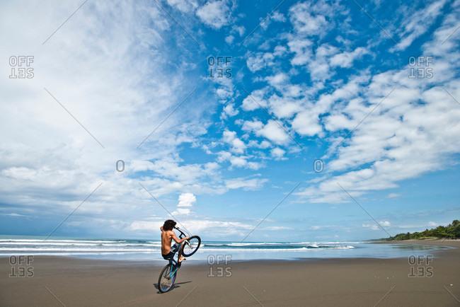 A Costa Rican boy rides his bike on a desolate beach