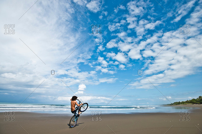 A Costa Rican boy rides his bike on a desolate beach