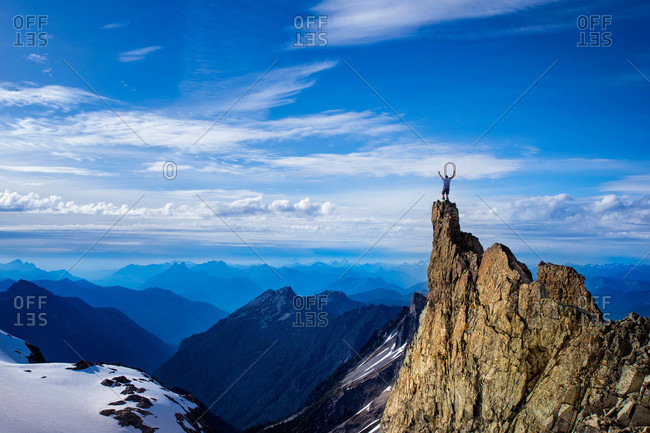 Man stands on a rocky point above the Lynch Glacier Clouds