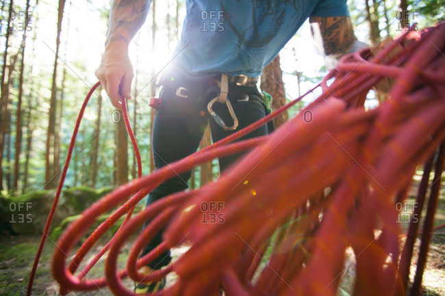 A climber works to coil his rope after a day of sport climbing