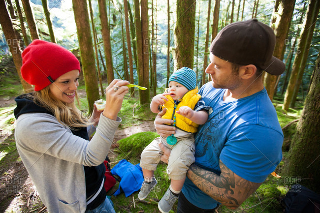 A mother and father feed their baby boy while in the outdoors