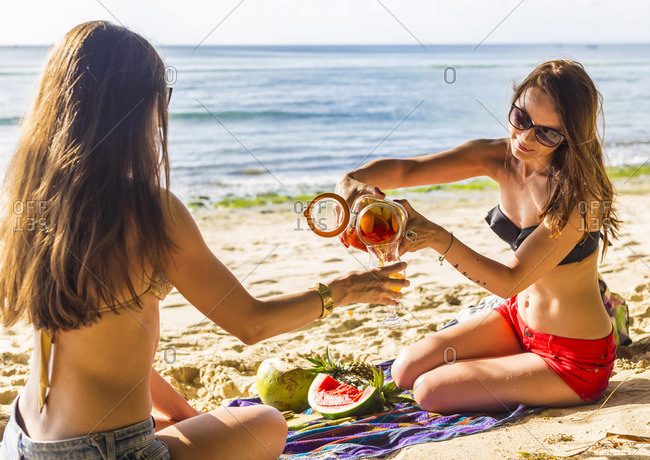 Two girls have a fun with sangria at the beach