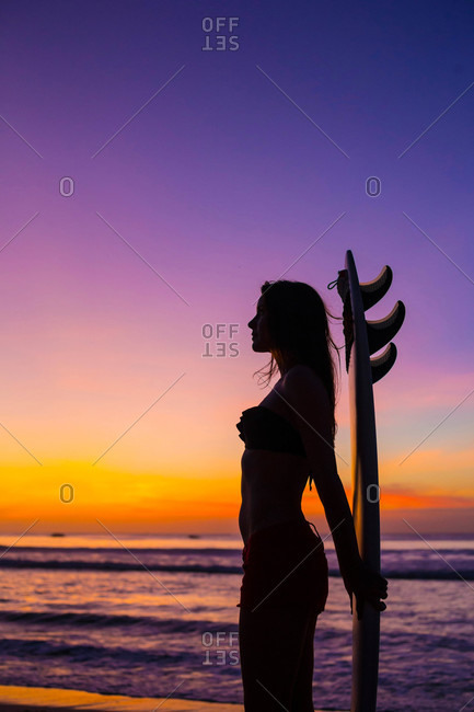 Silhouette of woman by the ocean with surf board