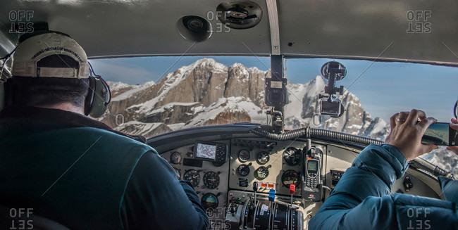 A small plane flys over the Alaska Range from Talkeetna Alaska