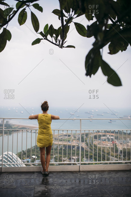 Woman standing at a railing overlooking a coastal city