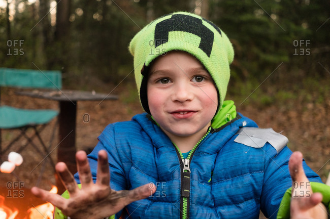 Boy with dirt covered hands at campground